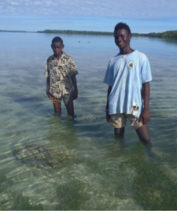 Local boys show the location of a heavily encrusted piece of ordnance in shallow water.